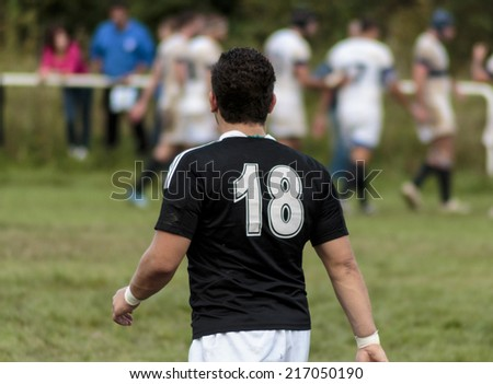 ZAGREB, CROATIA - SEPTEMBER 13, 2014: Rugby match Rugby Club Zagreb in white jersey and Rugby Club Sinj in black jersey. Unidentified player walking on field