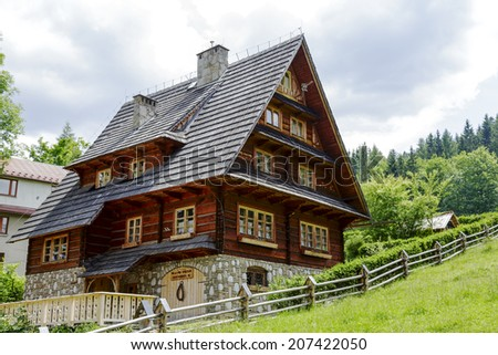 ZAKOPANE, POLAND - JUNE 28, 2014: Villa Pod Smrekami, house made of wooden logs with elements of Zakopane style, located in the part of Zakopane called Jaszczorowka, offers 17 beds in 6 rooms - stock photo