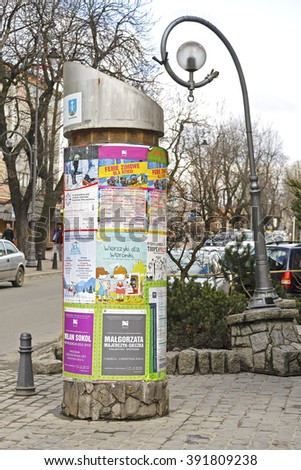ZAKOPANE, POLAND - MARCH 09, 2016: Advertising column placed next to Krupowki street. An advertising column presents posters and billboards on it. Advertising pillar is one way of outdoor advertising - stock photo