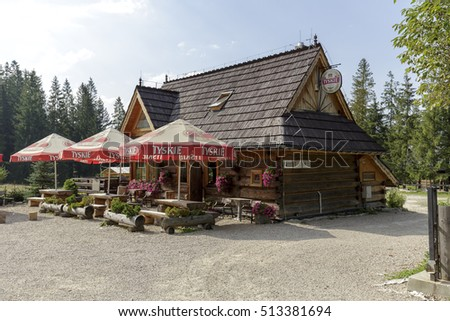 ZAKOPANE, POLAND - SEPTEMBER 12, 2016: Building in the style of mountain cottage it houses the restaurant. In front of the building there are benches and tables and umbrellas are spread above