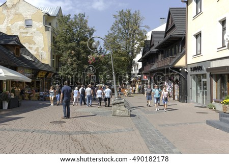 ZAKOPANE, POLAND - SEPTEMBER 12, 2016: Unidentified tourists walks along Krupowki street that is the most known pedestrian zone and shopping area in the city