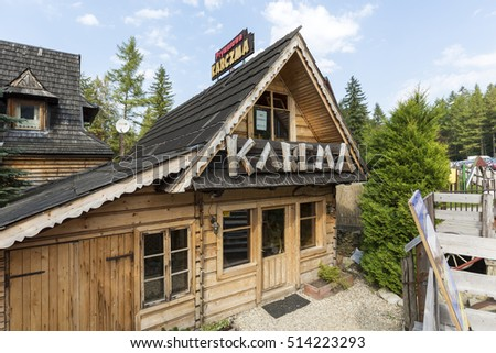 ZAKOPANE, POLAND - SEPTEMBER 12, 2016: Wooden building architecture is reminiscent of the style of the region. Large lettering defines the use of the building, this is regional restaurant