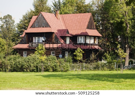 ZAKOPANE, POLAND - SEPTEMBER 13, 2016: Wooden dwelling house that probably was built in 1920. This building is surrounded with lots of shrubs and trees
