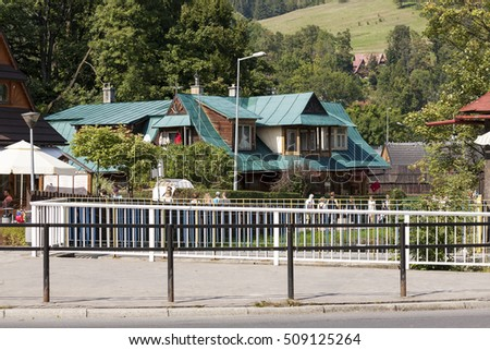 ZAKOPANE, POLAND - SEPTEMBER 12, 2016: Wooden villa covered with a tin roof painted green is a traditional building which was built in the old style of the region. Nowadays it houses art gallery