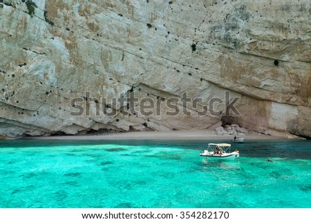 Zakynthos, Greece - August 11, 2015: Fishing boat at the Blue caves of Zakynthos island, Greece. Sunrays reflect through blue sea water from white limestones creating visual lighting effects.