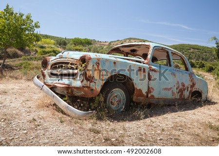 Zakynthos, Greece - August 20, 2016: Old abandoned rusted retro car stands in summer garden