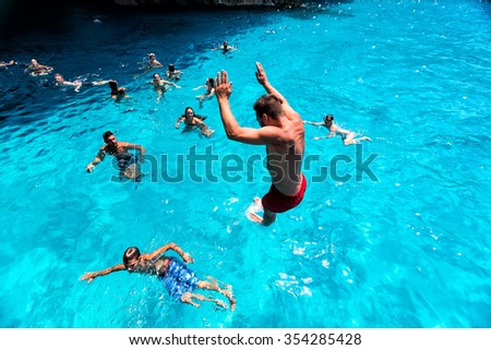 Zakynthos, Greece - August 11, 2015: Tourists enjoying the clear water of Zakynthos island, in Greece. Navagio Beach is a popular attraction among tourists visiting the island of Zakynthos - stock photo