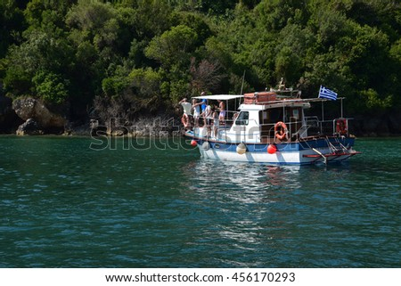 ZAKYNTHOS, GREECE - JULY 5, 2015: People on fishing boat have spotted a caretta sea turtle swimming in the shallows close to Keri beach in the national sea park of Zakynthos, Greece.