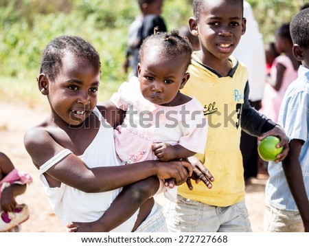 ZANZIBAR, TANZANIA - AUGUST 31, 2014: Local children asking people to take photos of them in one of the villages on Zanzibar island, Tanzania, East Africa. Horizontal orientation, - stock photo