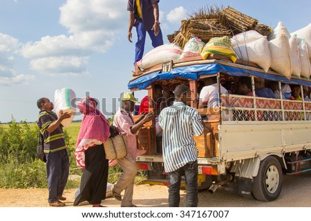 ZANZIBAR, TANZANIA - CIRCA JULY 2013: People loading cargo and luggage on local public transport vehicle known as Daladala, on July 2013. Daladalas are cheap crowded minibuses operating on the island.