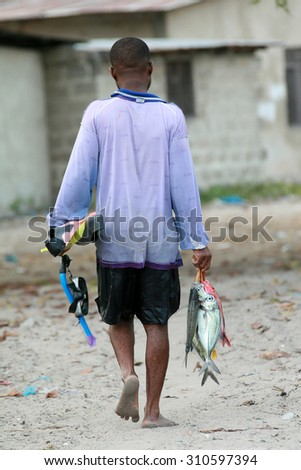 Zanzibar, Tanzania - February 18, 2008: Fisherman diver returns home with their catch, carries a caught fish.