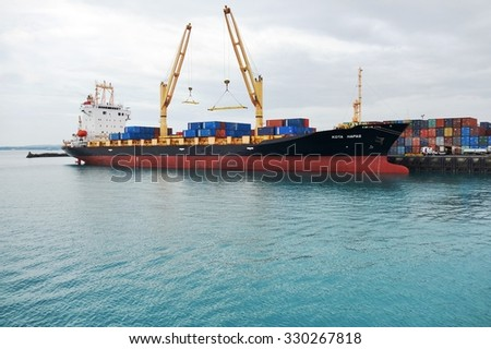 ZANZIBAR, TANZANIA -18 JUNE 2015- A container ship and stacked containers in the port of Zanzibar, an island in Tanzania in Africa.