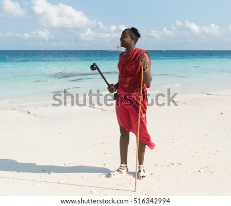 ZANZIBAR, TANZANIYA- JULY 17: smiling masai on a beach and blue sea on the background on July 17, 2016 in Zanzibar