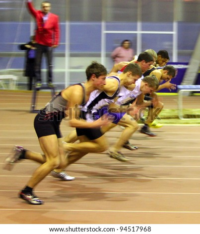 ZAPORIZHIA, UKRAINE - JAN 30: Unidentified boys, age group - 17, on the start of the 60 meters dash during the Ukainian Junior Track and Field Championships on January 30, 2012 in Zaporizhia, Ukraine. - stock photo