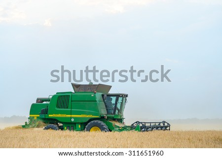 ZAPORIZHZHYA, UKRAINE - July 28, 2015: John Deere Combine Harvester Harvesting Wheat in the Field. - stock photo