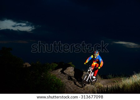 ZAPORIZHZHYA, UKRAINE - JUNE 16, 2015: Fully Equipped Professional Downhill Cyclist Riding the Bike on the Night Rocky Trail. Extreme Sports - stock photo
