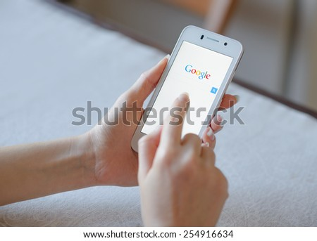 ZAPORIZHZHYA, UKRAINE - NOVEMBER 21, 2014: Young Woman Using Google Web Search on her Smart Phone. - stock photo