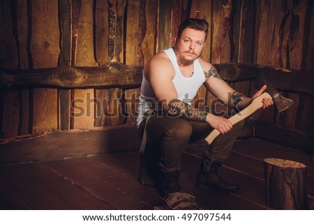 Zaporozhye, Ukraine - March 27, 2016: Style lumberjack. Woodcutter with a beard, mustache and tattoos, wearing a white T-shirt, pants and suspenders with an ax on a wooden background.
