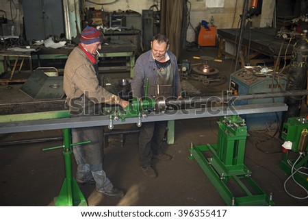 ZAPOROZHYE, UKRAINE - OCTOBER 21: The boss with the workers tests new machine for pipe bending at the Ukrainian plant on October 21, 2013 in Zaporozhye, Ukraine.