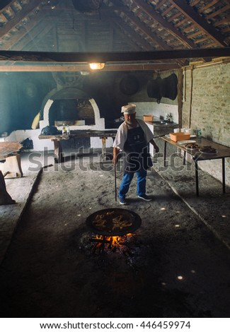 ZASAVICA-JUNE 04 :man preparing steak on June 04, 2016 in Zasavica,Serbia