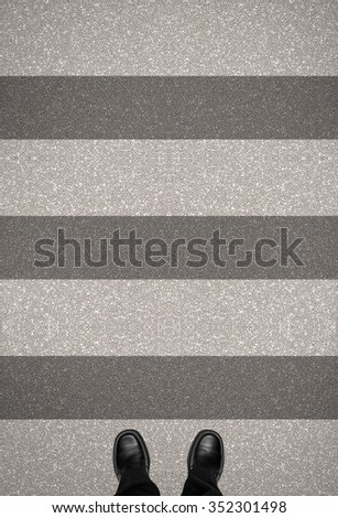 Zebra crossing on road with business man shoes standing, top view, looking down - stock photo