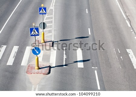 Zebra pattern pedestrian crossing with some road signs - stock photo