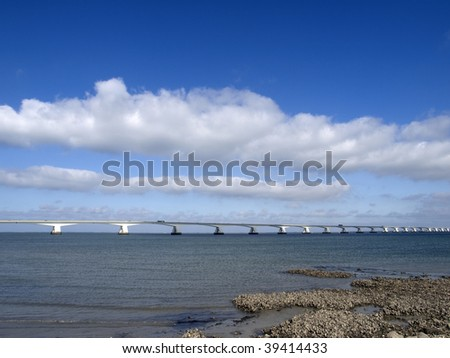 Zeeland bridge, the longest bridge in the Netherlands (5022 mtr) with wild oysters on the foreground
