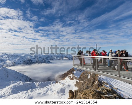 Zell am See - December 6, 2014: People take pictures on the viewing platform at the ski resort at an altitude of 3000 m on the glacier Kitssteynhorn of 6 December 2014, Zell am See, Kaprun, Austria - stock photo