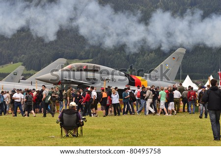 ZELTWEG, AUSTRIA - JULY 01: crowd of spectators and different jets by airshow - airpower11 - on July 01, 2011 in Zeltweg, Austria