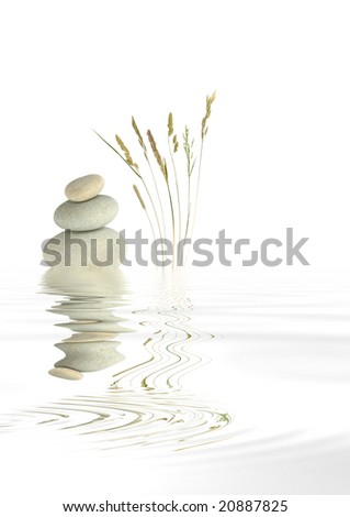 Zen abstract of natural grey spa stones balanced on top of each other, with wild grass stalks and reflection over rippled water, against white background. - stock photo