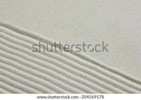 Zen background of raked sand with diagonal parallel lines on the lower half of the frame and smooth sand with copyspace above. - stock photo