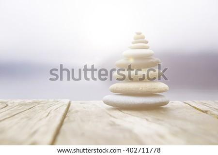 Zen balancing pebbles next to a misty lake. - stock photo