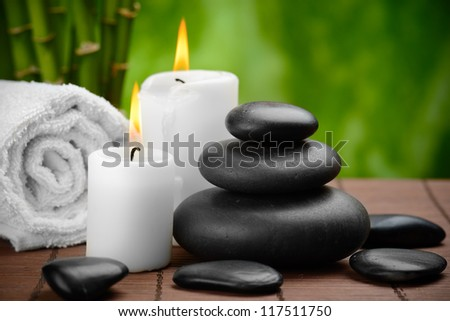 zen basalt stones and candle on the wooden mat