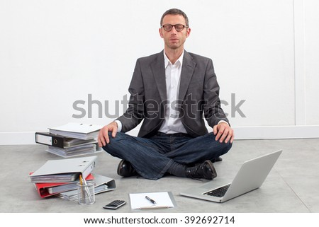 zen business concept - serene businessman meditating at the office, sitting crossed legs, having a break in working on his budget