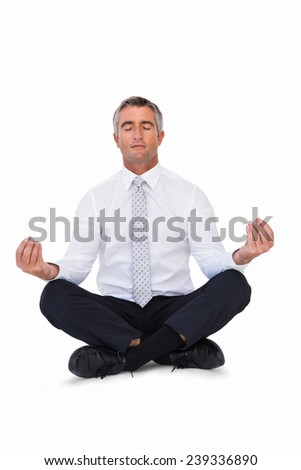 Zen businessman meditating in lotus pose on white background