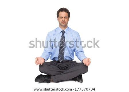 Zen businessman meditating in lotus pose with eyes closed on white background - stock photo
