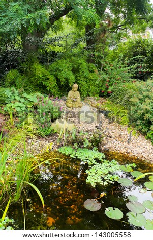 Zen garden with green  plants and Buddha statue - stock photo