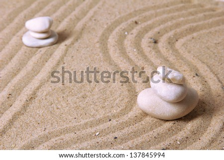 Zen garden with raked sand and round stones close up - stock photo