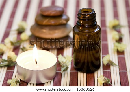 Zen like balanced stones, dried flower, essential oil and candle on bamboo background.
