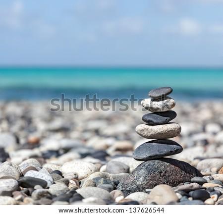 Zen meditation background -  balanced stones stack close up on sea beach - stock photo