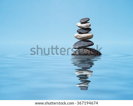 Zen meditation relaxation peacefulness peace of mind concept background -  balanced stones stack in water with reflection - stock photo