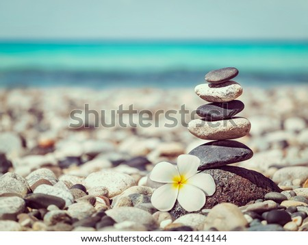 Zen meditation spa relaxation background - vintage retro effect filtered hipster style image of   balanced stones stack with frangipani plumeria flower close up on sea beach - stock photo