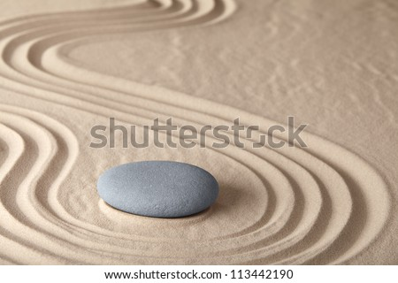 Zen meditation stone traditional Japanese garden with sand and rock pattern concept for simplicity harmony and serenity helps in concentration and relaxation - stock photo
