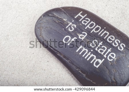 "Zen picture of ""Happiness is a state of Mind"" message engraved on a stone in the sand"