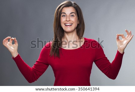 zen relaxation - laughing 30s beautiful woman meditating, relaxing with yoga technique, finding exciting business ideas, studio gray background - stock photo