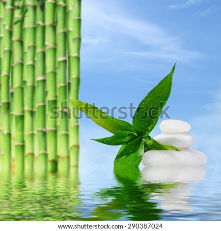 Zen spa concept background - Zen massage stones and bamboo reflected in water - stock photo