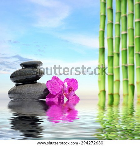 Zen spa concept background-Zen massage stones and bamboo reflected in water - stock photo