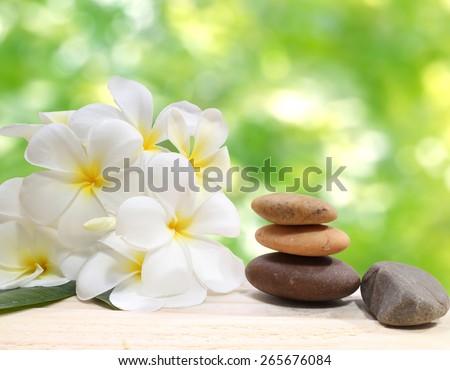 Zen spa concept background - Zen massage stones with frangipani plumeria flower  - stock photo