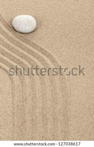 zen stone in soft sand with lines