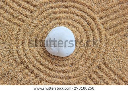 Zen stone on raked sand - stock photo